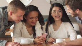 Quatro amigos olham algo no smartphone no café fotografia de stock royalty free