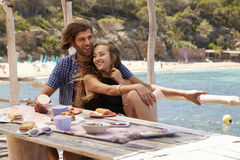 Quatro amigos que falam em uma tabela pelo mar, Ibiza, Espanha fotografia de stock royalty free