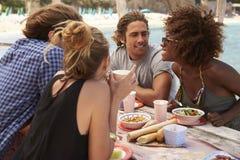 Quatro amigos que falam em uma tabela pelo mar, vista lateral, Ibiza foto de stock royalty free