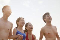 Quatro amigos que sorriem e que riem na praia fotografia de stock