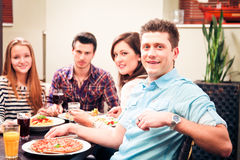 Quatro amigos que têm o almoço em um restaurante Fotos de Stock Royalty Free