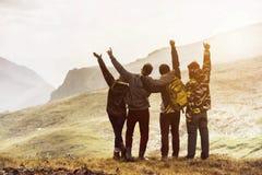 Quatro amigos que têm o por do sol da montanha do divertimento Foto de Stock