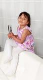 Quatro anos de menina idosa que senta-se no sofá branco Foto de Stock