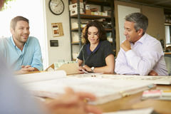 Quatro arquitetos que sentam-se em torno da tabela que tem a reunião foto de stock