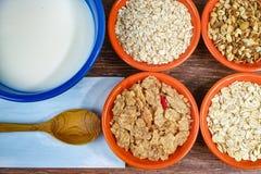 Quatro bacias pequenas com cereais diferentes e bacia com leite, alimento saudável Fotos de Stock Royalty Free