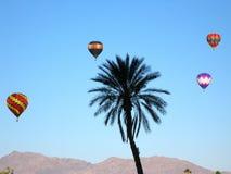 Quatro balões de ar quente que flutuam contra o céu azul imagem de stock royalty free