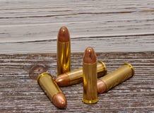Quatro balas do revólver com um fundo de madeira Fotos de Stock
