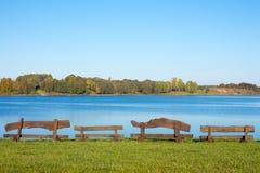 Quatro bancos de madeira no lago imagens de stock royalty free