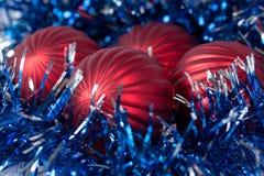 Quatro bolas dos cristmas estão encontrando-se em um ouropel Fotos de Stock Royalty Free