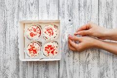 Quatro bolos do bolo em uma caixa nas placas velhas brancas do fundo do vintage A menina puxa a fita imagens de stock