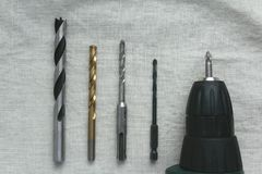 Quatro brocas para trabalhar com materiais diferentes e uma chave de fenda estão na tela fotos de stock royalty free