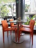 Quatro cadeiras alaranjadas com uma tabela de Dinning Fotos de Stock