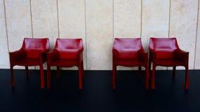 Quatro cadeiras vermelhas no assoalho preto perto da parede branca imagem de stock royalty free