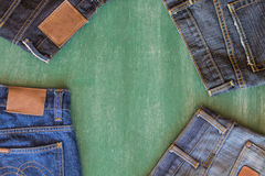 Quatro calças de brim com fundo do quadro Fotos de Stock Royalty Free