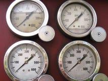 Quatro calibres de pressão aço-orlarados no fundo marrom-vermelho Foto de Stock