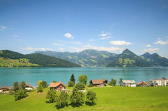 Quatro camadas de uma paisagem suíça: campos, lagos, montanhas e céu azul fotografia de stock royalty free
