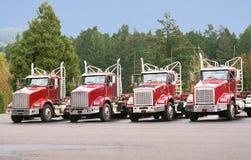 Quatro caminhões do arrasto de log na jarda da manutenção. Imagem de Stock