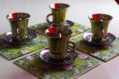 Quatro canecas de café com os pires na tabela fotos de stock