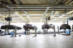 Quatro carros pretos aumentados em elevadores na garagem Fotos de Stock Royalty Free