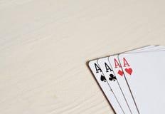 quatro cartões de jogo das mãos de pôquer dos áss em um fundo claro da mesa Fotos de Stock Royalty Free