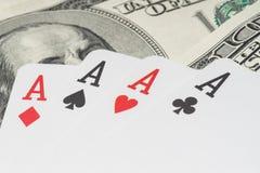 Quatro cartões de jogo do pôquer dos áss entre U S Dólares Imagens de Stock