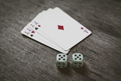 Quatro cartões de jogo dos áss e dois dados numeram o dobro cinco em um fundo de madeira risco, sorte, abstração Imagem de Stock