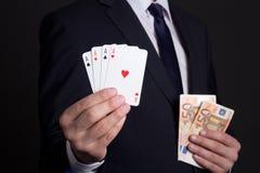 Quatro cartões e dinheiros dos áss equipam dentro as mãos Fotografia de Stock Royalty Free