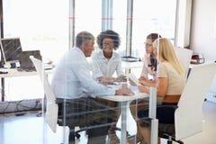 Quatro colegas que encontram-se em torno de uma tabela em um escritório imagens de stock