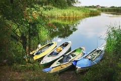 Quatro coloriram barcos na costa do rio pequeno imagens de stock