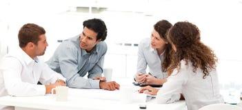 Quatro coordenadores que discutem sobre um projeto novo Imagens de Stock Royalty Free
