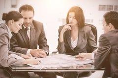 Quatro coordenadores sérios que olham os planos que sentam-se em uma tabela fotos de stock royalty free