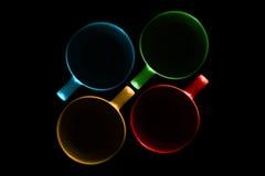 Quatro copos de cores diferentes fotografia de stock
