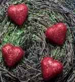 Quatro corações em um fundo do musgo Fotos de Stock Royalty Free