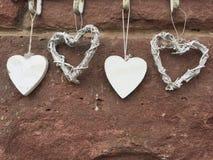 Quatro corações que penduram em uma parede Imagem de Stock Royalty Free