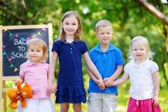 Quatro crianças adoráveis estão indo para trás à escola fotos de stock royalty free