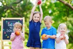 Quatro crianças adoráveis estão indo para trás à escola imagem de stock