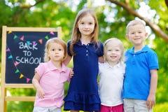 Quatro crianças adoráveis estão indo para trás à escola fotografia de stock