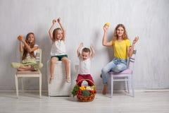 Quatro crianças com alimento saudável dos legumes frescos foto de stock royalty free