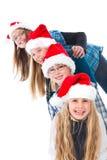 Quatro crianças com riso dos chapéus do Natal Fotos de Stock