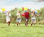 Quatro crianças de riso que correm no gramado verde imagens de stock