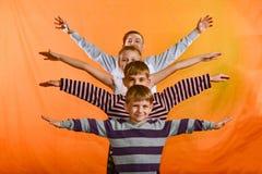 Quatro crianças estão em seguido e levantam suas mãos para os lados na idade de um fundo amarelo, mais novos olham para fora para fotografia de stock