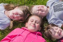 Quatro crianças na grama, fora imagem de stock royalty free