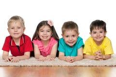 Quatro crianças no tapete branco fotos de stock royalty free