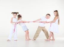Quatro crianças pequenas na tração branca picam a corda. Imagens de Stock