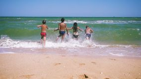 Quatro crian?as que correm ao mar da praia video estoque