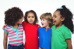 Quatro crianças que estão junto em uma linha Imagem de Stock