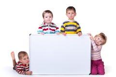 Quatro crianças que prendem uma placa branca Imagem de Stock Royalty Free