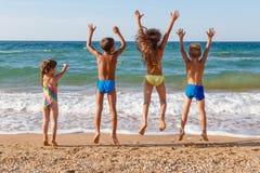 Quatro crianças que saltam na praia fotografia de stock