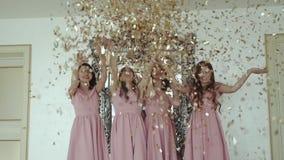 Quatro damas de honra felizes no vestido de noite que joga acima envoltórios dourados dentro filme