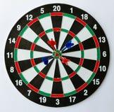 Quatro dardos em um bullseye imagem de stock